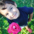 Stock Photo: Happy beautiful child on ground with rose outdoor