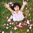 Happy beautiful girl on ground with rose's petals — Photo