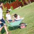 Dad in white driving boys on the wheelbarrow — Stock Photo
