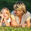 Child with mother happiness on green meadow in summer time - Stock Photo