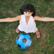 Little nice girl playing with a ball in air - Stock Photo