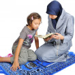 Young nice muslim female teaching her daughter — Stock Photo #9992428