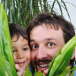 Happy father and his son hiding behind green leaf — Stok fotoğraf
