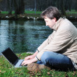 Young man with laptop outdoor — Stok fotoğraf