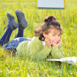 Royalty-Free Stock Photo: Cute girl reading on meadow with board behind