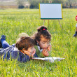 Playing and reading on meadow - Stock Photo