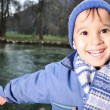 Positive kid beside the river — Stock Photo