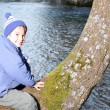 Kid on tree beside the river - Stock Photo