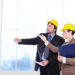 Man and woman with blueprints on work place — Stock Photo