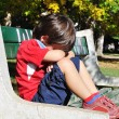 Sad child in the park, outdoor, summer to fall - Stock Photo