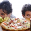 Two children with surprised face on pizza table — Stock Photo