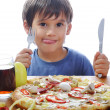 Cute little boy eating pizza on table, isolated — Foto Stock