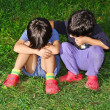 Two cute children sitting on ground, consoling each other — Stock Photo