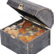 Many coins in one old chest isolated — Stock Photo