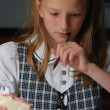 Stock Photo: Little cute girl in classroom, writting and eating
