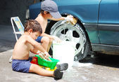 A little cute kid is cleaning car, outdoor — Stock Photo