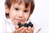 Little cute white kid with blackberry in hands — Stock Photo