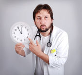 Male doctor holding out an alarm clock ticking ever closer to 12 — Stock Photo