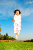 Little girl jumping against beautiful sky — Stock Photo