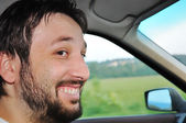 Young male with beard driving a car and smiling — Stock Photo