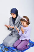 Young muslim woman praying on traditional way with her daughter — Stock Photo