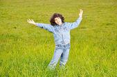En liten söt glad flicka stående på grön mark — Stockfoto
