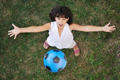 Little nice girl playing with a ball in air — Stock Photo