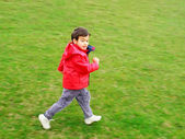 Cute boy running on green meadow — Stock Photo