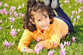 与周围的粉红色花草甸的女孩 — 图库照片