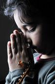 Chica rezando en la oscuridad — Foto de Stock