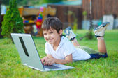 Cute kid is laying on laptop in beautiful environment — Stock Photo