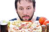 Adult person with surprised face on pizza table — Stock Photo