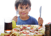 Cute little boy eating pizza on table, isolated — Stock Photo