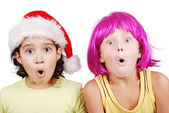 Funny cute boy with pink periwig on head and santa girl — Stock Photo