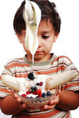 Very cute kid is about to eat very sweet mixed fruint and cream — Stock Photo