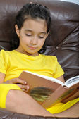 Little beautiful girl in yellow reading book in sofa — Stock Photo