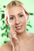 Woman applying moisturizer cream on the face — Stock Photo