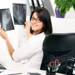 Young woman doctor is looking at xray — Stock Photo #8447611