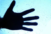 Silhouette of human hand over glass with drops — Stock Photo