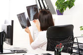 Young woman doctor is looking at xray — Stock Photo