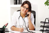 Young woman doctor talking by phone — Stock Photo