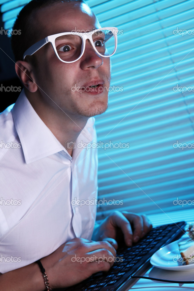 Funny nerd in glasses surfs internet at night time — Stock Photo #8446331