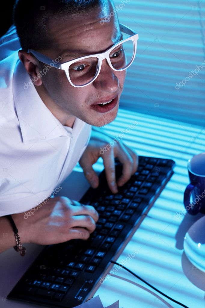Funny nerd in glasses surfs internet at night time — Stock Photo #8446360