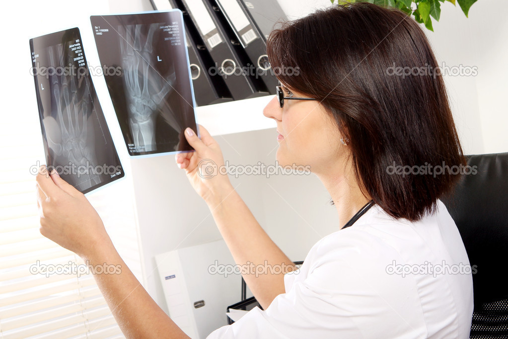 Young woman doctor is looking at xray of broken hand — Stock Photo #8447601