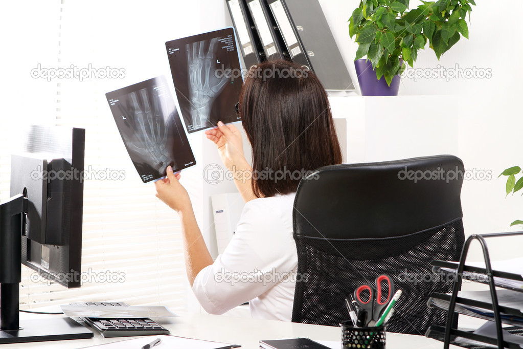 Young woman doctor is looking at xray of broken hand  Stock Photo #8447614