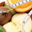 Fresh fruits and measure tape — Stock Photo