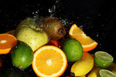 Fresh fruits and water splashes — Stock Photo