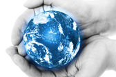 Blue planet in hands — Stock Photo