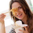 Happy woman eating noodles - Stock Photo
