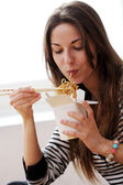 Happy woman eating noodles — Stock Photo